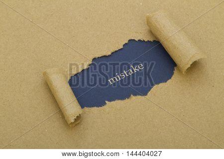 Mistake word written under brown torn paper