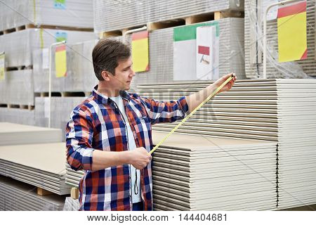 Man Measures With Roulette Drywall Sheets In Store Building Materials