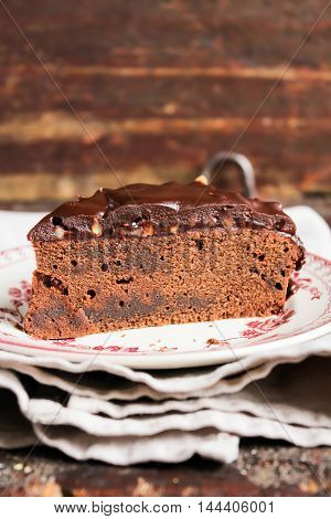 Piece of dark chocolate cake with chocolate frosting, walnuts and raspberry jam, selective focus
