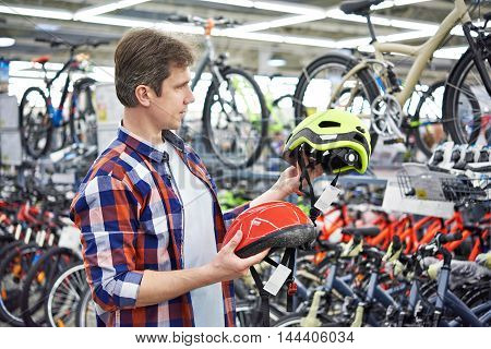 Man Chooses Helmet For Cycling