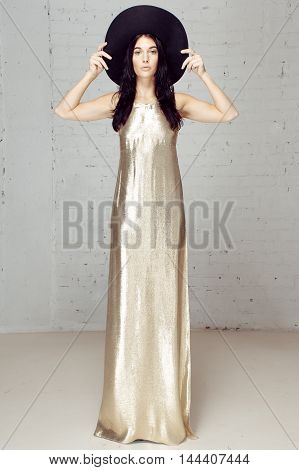 The girl in gold dress and black hat. Beautiful young women dressed in white long dress in studio with brick wall