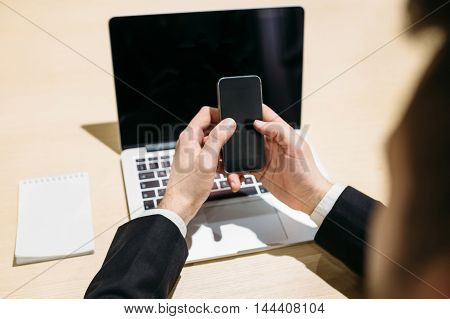 Business concept male hand laptop phone work