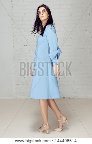 Girl in a blue dress shirt and pink glasses turns around, looks back. Model in studio looking upward. Studio has grey bricks wall
