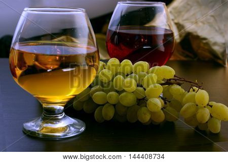 white and red wine in a glass with grapes on the table