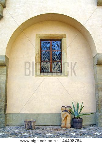 Arched courtyard wall with decorative succulent pot plant and wooden sculpture. Spanish, mediterranean style