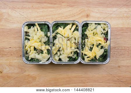 Putting cheese to spinach box before bake / cooking Baked spinach concept