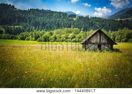 Old wooden farm house in the Austrian countryside bycicle road from San Candido to Lienz