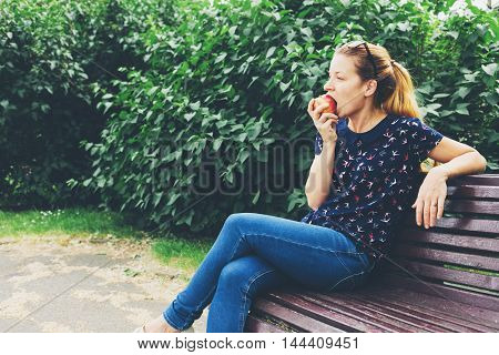 Young woman eating an aple in the park