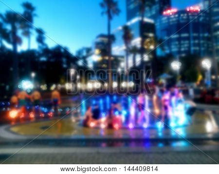 Children playing among the water fountain at water park. Blurred background.