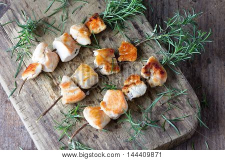 Chicken brochette kebab grilled bbq chicken meat on rosemary branch on rustic cutting board and rosemary bunch on wooden background