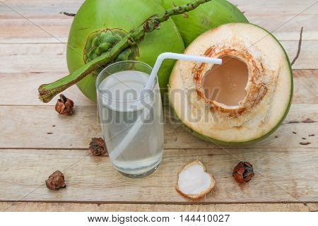 Fresh Coconut Water Drink in glass with straw on wooden  background