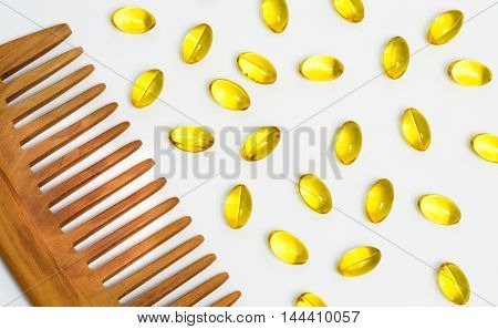 Wooden hair comb with yellow macro pills on light background, closeup, top view.