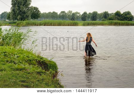 Young fully dressed woman walks into the water of a natural pond. It's a gray and gloomy day
