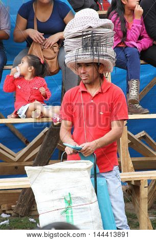 Cajamarca Peru - February 8 2016: Young man sells women's hats at Carnival parade in Cajamarca Peru on February 8 2016