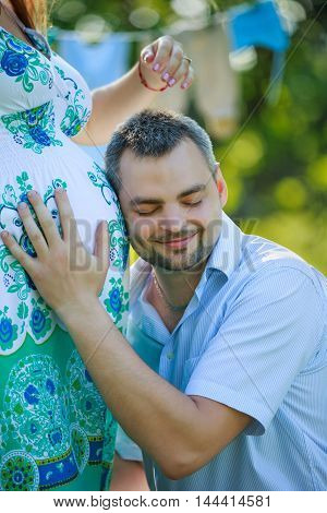 Happy expectant father listening to the belly of his pregnant wife on the nature