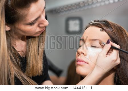 Make-up professional working with model, toned image