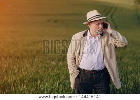 an elderly man walks pool and talking on the phone