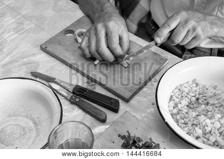 Male hands chopping fresh beans sitiing in the kitchen indoors cropped shot in black and white