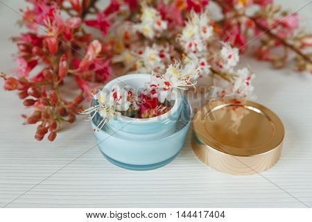 There White and Pink  Branches of Chestnut Tree with Open Blue and Golden Jar of Cream are on White Table,Selective Focus