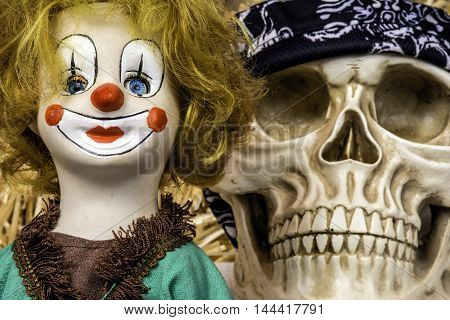 antique porcelain clown doll with scary human skull looking over its shoulder
