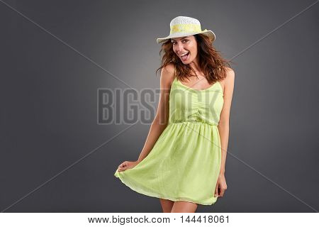 A beautiful young woman feeling happy in a green dress and a hat