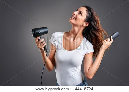 A beautiful young woman feeling happy while using a hairdryer and a hairbrush