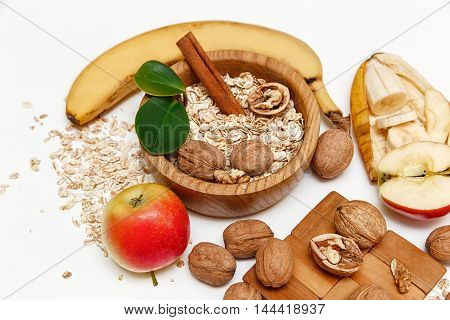 There are Banana,Apple,Walnuts in the Wooden Plate and Rolled Oats,Wooden SpoonTrivet with Green Leaves.Healthy Fresh Organic Food on the White Background