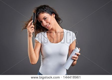A beautiful young woman fixing her hair using a hairspray and a hairbrush.