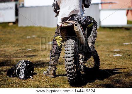 rear wheel of motorcycle racing lying next to a sports helmet