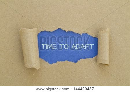 TIME TO ADAPT message written under torn paper.