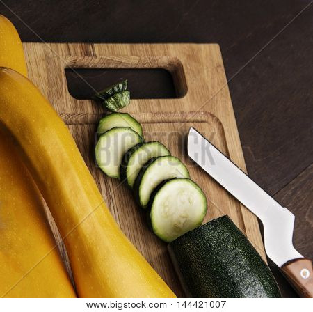 A fresh sliced zucchini on wooden kitchen desk with knife.wooden background.closeup