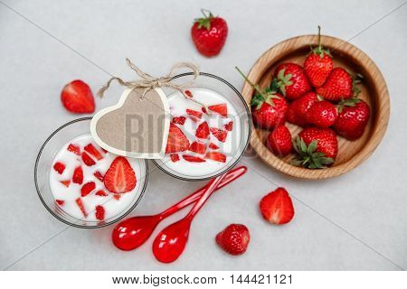 Two Glasses of Yogurt.Red Fresh Strawberries are in the Wooden Plate with Plastic Spoons.Wish Heart Card on the White Paper.Breakfast Organic Healthy Tasty Food.Cooking Vitamins Ingredients.Summer Fruits.Top View