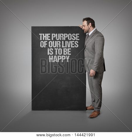 The purpose of our lives is to be happy text on blackboard with businessman standing side
