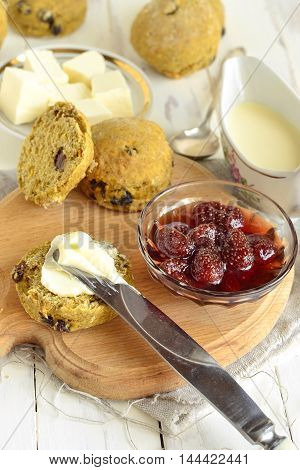 Pumpkin scones with dried fruit for breakfast served with jam and butter,  vertical