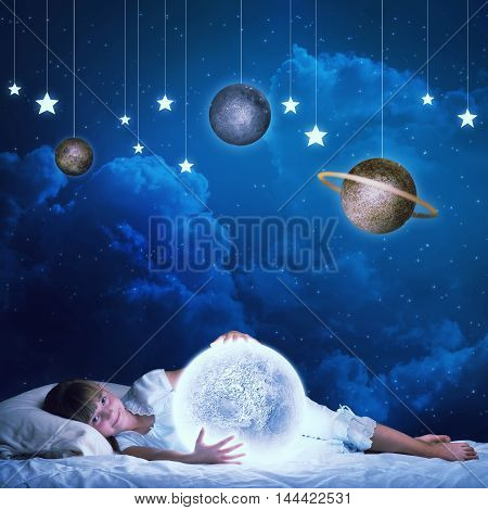Cute girl in bed holding a glowing moon planet. Elements of this image are furnished by NASA