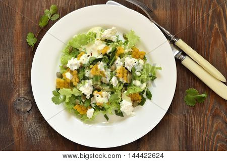 Salad with corn greens feta with mayonnaise sauce, top view