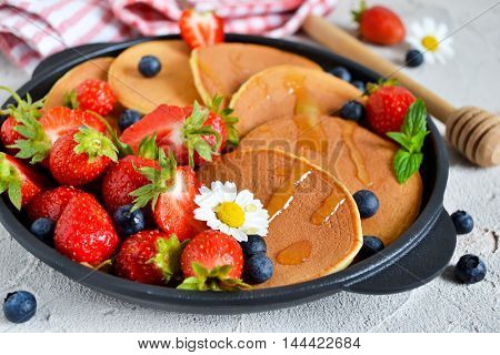 Pancakes with berries and honey in a pan on a concrete background