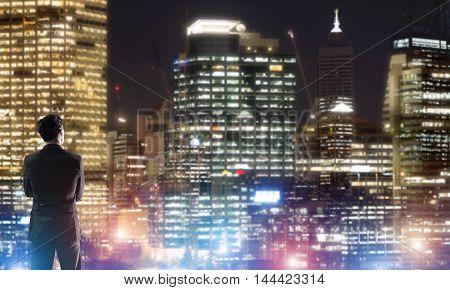 Elegant businessman in a dark suit looking at night city