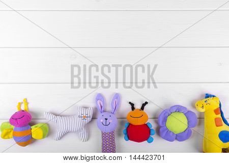 stuffed baby toys on wooden background with copy space