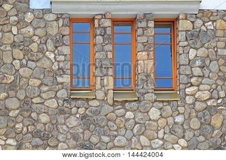 Stone House Exterior With Three Vertical Windows