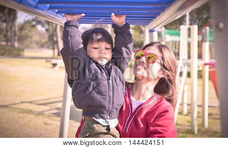 Mother is helping a child on playground Bars