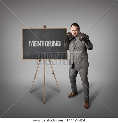 Mentoring text on  blackboard with businessman wearing boxing gloves