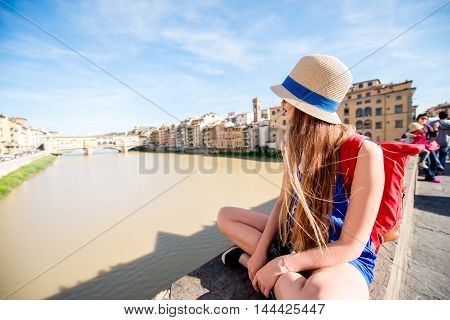 Young female traveler enjoying the view on the famous Ponte Vecchio bridge in Florence city