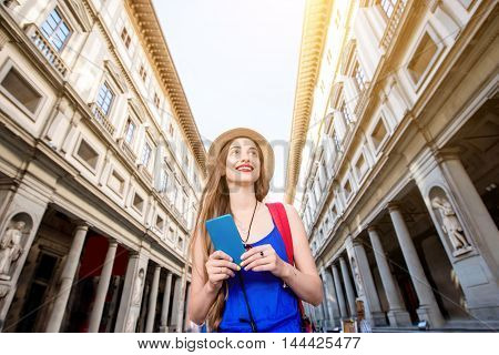 Young female traveler with phone near famous Uffizi museum in Florence. Vacation in Italy