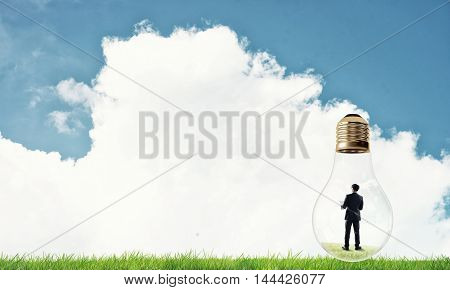 Businessman inside glass light bulb outdoors looking away at blue sky and white clouds