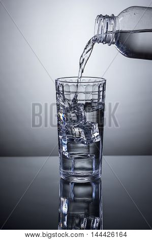 Water being poured from a bottle into a glass of ice.