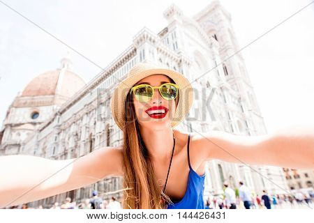 Young smiling woman in blue dress making selfie photo in front of Santa Maria del Fiore cathedral in Florence. Having great vacations in Italy