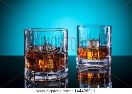 A couple glasses of liquor in a studio setting.