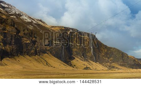 Beautiful Landscape of Icelandic mountain with show cover on top and clear blue sky during late winter