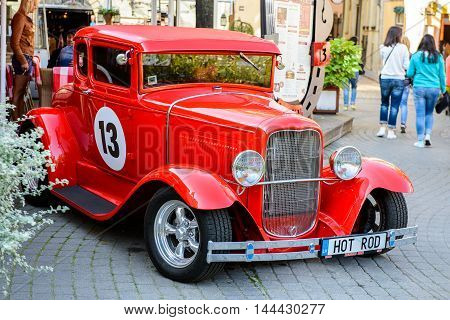 RIGA, LATVIA - SEP 7, 2014:  Red old car in the Old Town of Riga. Riga's historical centre is a UNESCO World Heritage Site